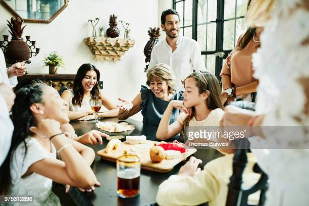 Laughing grandmother sharing drinks and food with family while telling stories during party