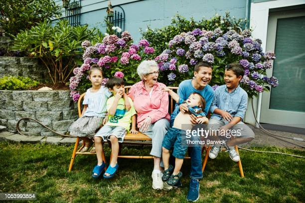 laughing great grandmother and great grandchildren sitting in backyard garden - naughty america stock pictures, royalty-free photos & images