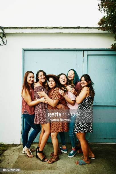 laughing group of female friends embracing in backyard - mittelgroße personengruppe stock-fotos und bilder