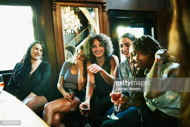 laughing group of female friends sharing drinks in bar - ladies' night stock pictures, royalty-free photos & images