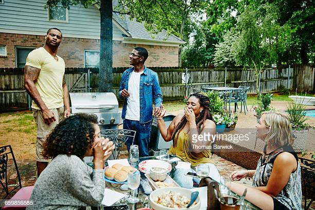 laughing group of friends barbecuing in backyard - funny bbq stock pictures, royalty-free photos & images