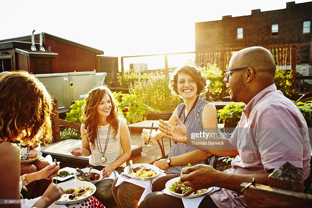 Laughing group of friends dining in rooftop garden : Photo