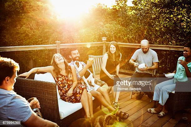 Laughing group of friends eating dinner on deck