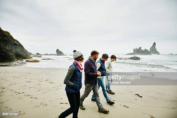 laughing group of friends exploring beach - trousers stock pictures, royalty-free photos & images