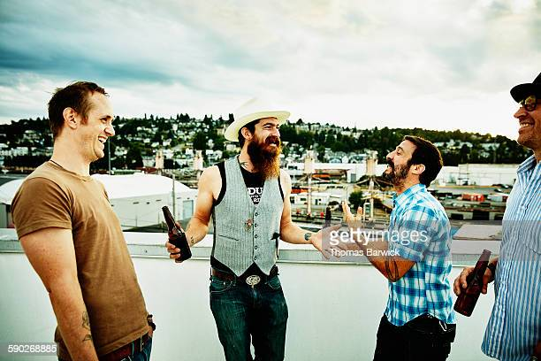 Laughing group of friends sharing beers on rooftop