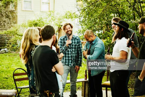 Laughing group of friends sharing drinks in backyard on summer evening