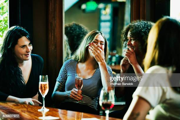 Laughing group of women enjoying drinks in bar