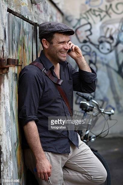 rindo bonito homem maduro com tampa plana no telefone - boina masculina - fotografias e filmes do acervo