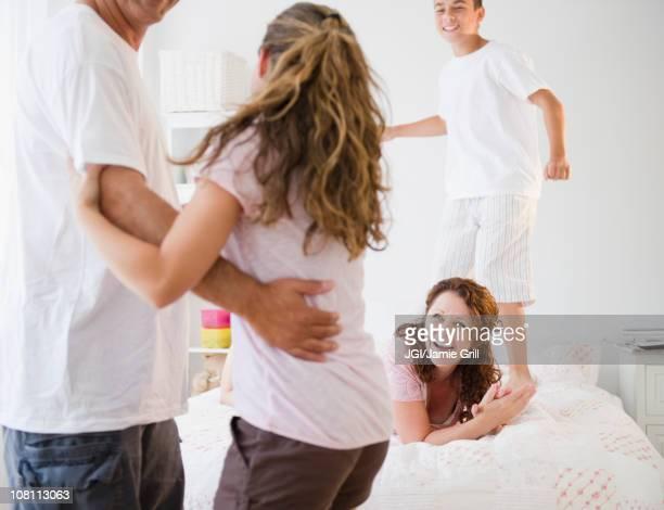 laughing hispanic family playing together - mom flirting 個照片及圖片檔