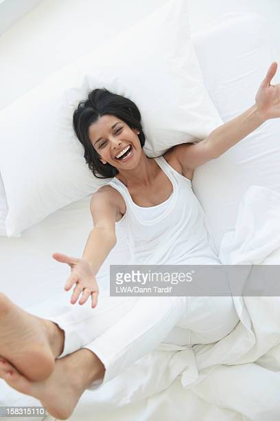 Laughing Hispanic woman laying in bed with arms outstretched