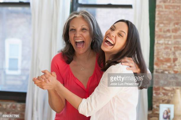 Laughing Hispanic women dancing