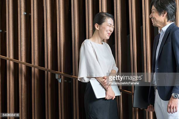 laughing japanese businesswoman with laptop, businessman with folder, office lobby - downtown comedy duo stock pictures, royalty-free photos & images