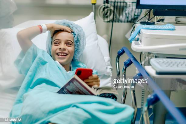laughing kid wearing cap and hospital gown while in bed - outpatient care stockfoto's en -beelden