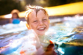 Laughing little boy playing in the swimming pool