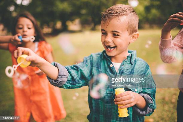Laughing little boy playing with bubbles in the park