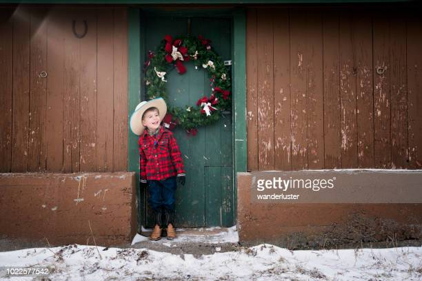 laughing little cowboy and christmas wreath - cowboy christmas stock pictures, royalty-free photos & images