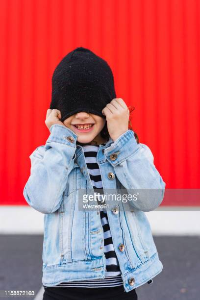 laughing little girl covering eyes with her black cap - funny black girl ストックフォトと画像