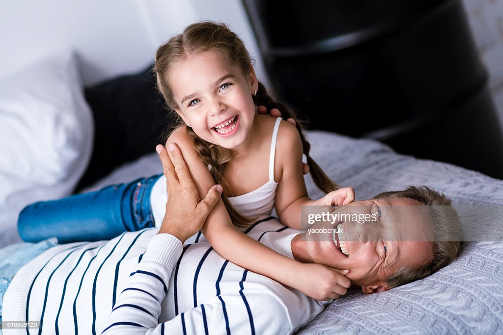 Laughing little girl having fun with her grandfather : Stock Photo