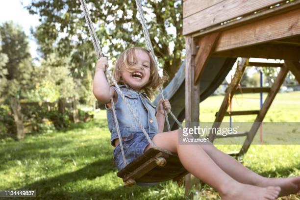 laughing little girl sitting on swing in the garden - ein mädchen allein stock-fotos und bilder