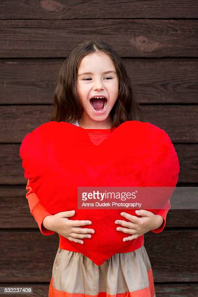 Laughing little girl with a red plush heart