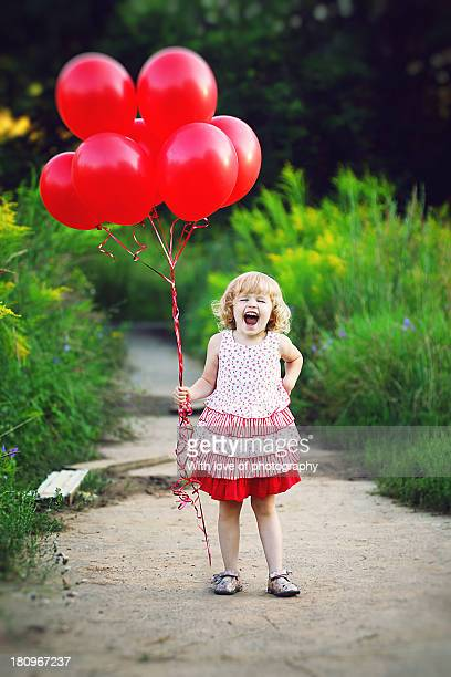 laughing little girl with balloons in summer