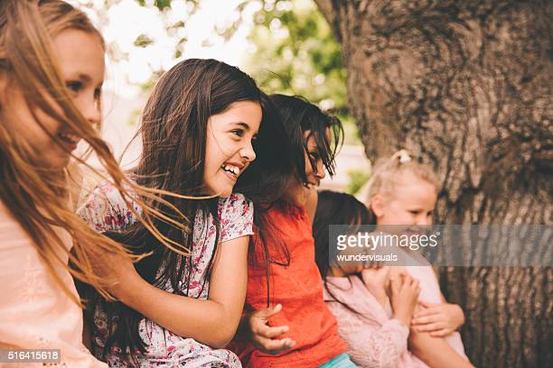 Laughing little girl with her friends in a park