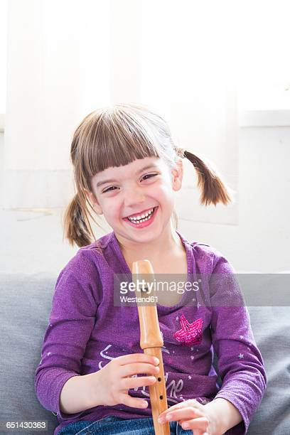 Laughing little girl with recorder at home