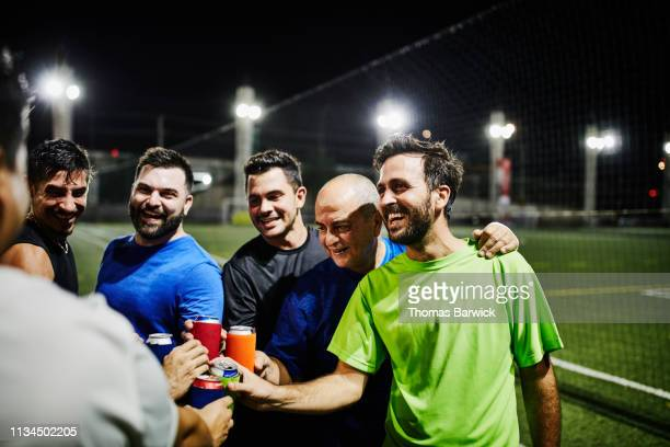 laughing male friends toasting with beers after nighttime soccer game - sportmannschaft stock-fotos und bilder