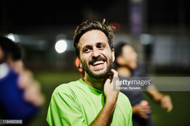 laughing male soccer player hanging out with friends after nighttime soccer game - 35 year old man stock pictures, royalty-free photos & images