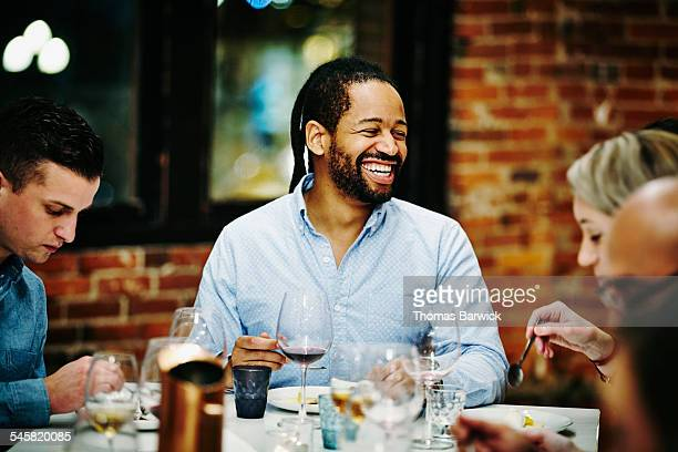 Laughing man at dinner party with friends