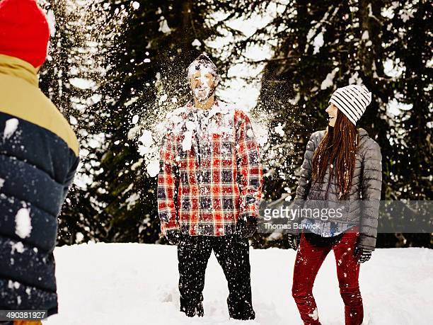 Laughing man being hit in the face by snowball