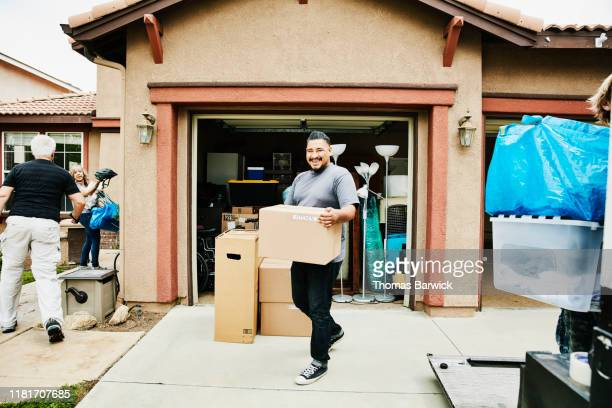 laughing man carrying box into new home on moving day - physical activity stock pictures, royalty-free photos & images