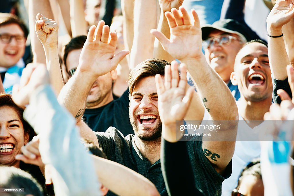 Laughing man cheering with crowd in stadium : Stock Photo