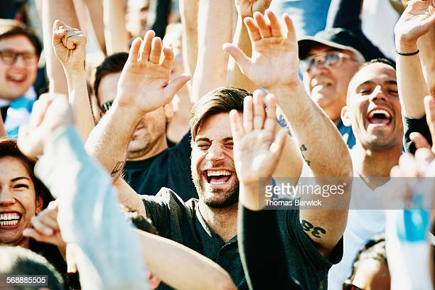 Laughing man cheering with crowd in stadium