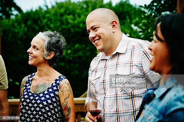 Laughing man drinking wine with friends on deck