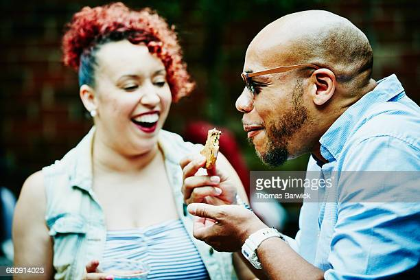 Laughing man eating cookie during party