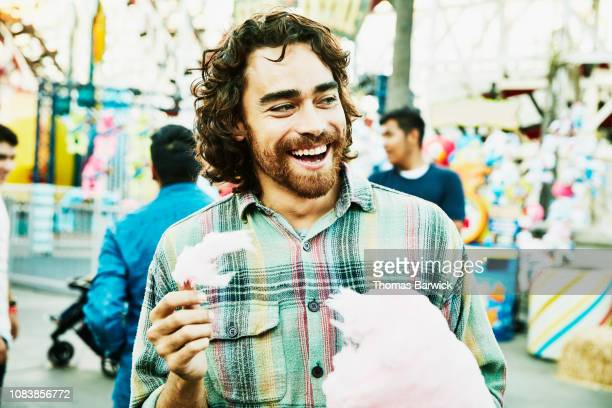 laughing man eating cotton candy in amusement park - only mid adult men stock pictures, royalty-free photos & images