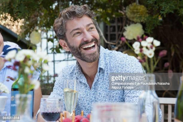 Laughing man enjoying family party on garden patio