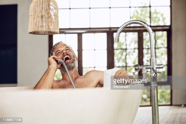 laughing man in bathtub using shower head as telephone receiver - homem tomando banho imagens e fotografias de stock