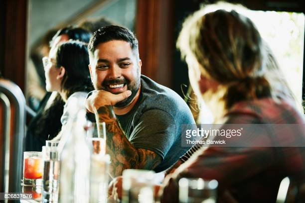 laughing man in discussion with friend while sitting at bar - bartresen stock-fotos und bilder