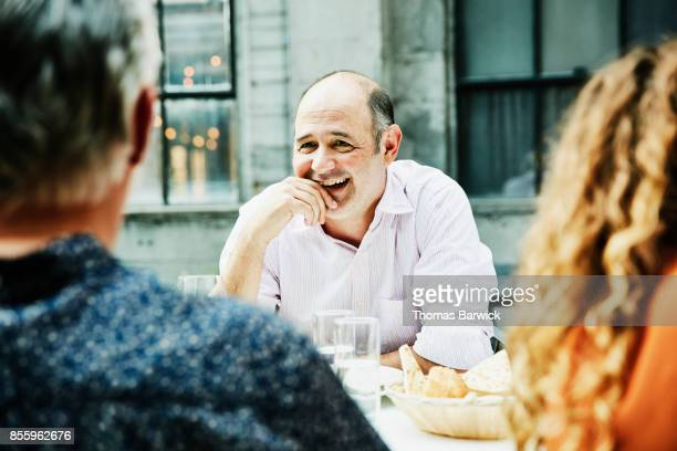 Laughing man in discussion with friends during celebration dinner