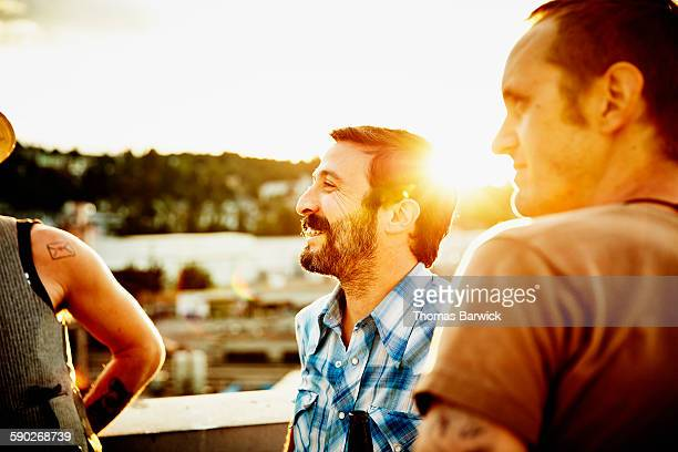 Laughing man in discussion with friends on rooftop