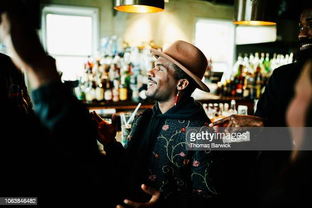 laughing man in discussion with friends while sitting in bar - handsome native american men stock pictures, royalty-free photos & images