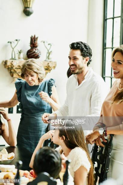 Laughing man sharing drinks and food with family gathered around dining room table