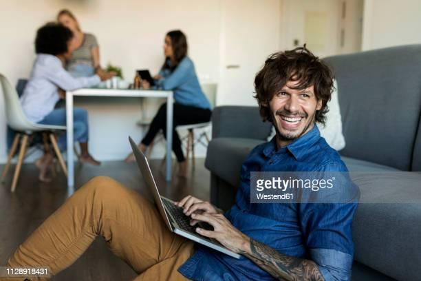 laughing man sitting on floor using laptop with friends in background - wegsehen stock-fotos und bilder