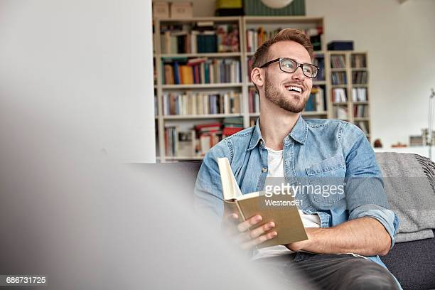 laughing man sitting with book on couch in the living room - seitenblick stock-fotos und bilder