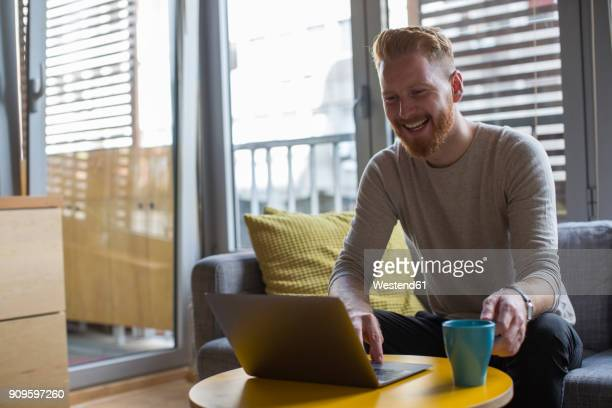 laughing man with coffee mug using laptop in his living room - solo un uomo foto e immagini stock