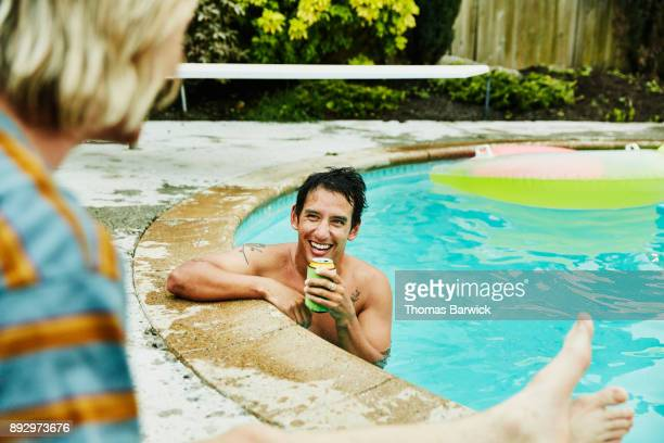 Laughing man with drink in backyard pool in discussion with friend on summer evening