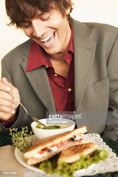 Laughing man with soup and sandwich