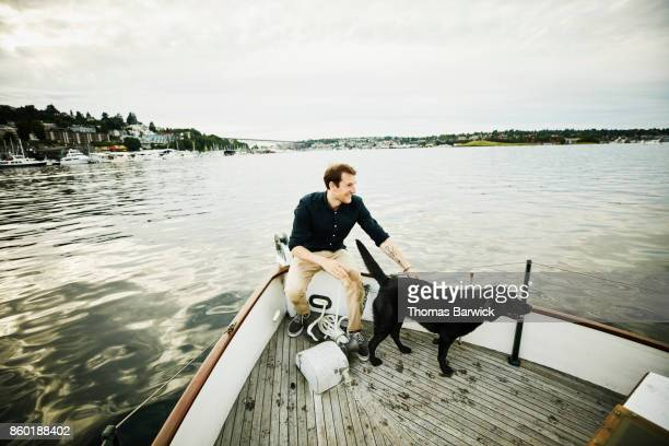 Laughing man with wet dog on bow of boat on summer evening